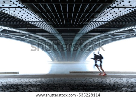 Anonymous male athletes running under a bridge in Lyon on a foggy winter day. Sports concept with motion blur and shallow focus.
