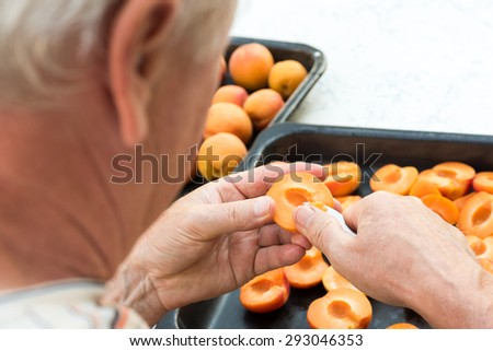 Anonymous man halving fresh homegrown apricots