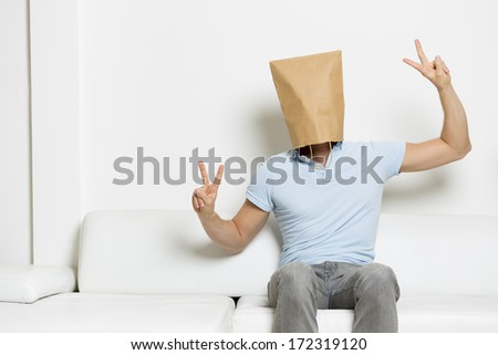 Anonymous man with head covered by a brown paper bag sitting on sofa and showing victory sign, empty space for text, on white background. - stock photo