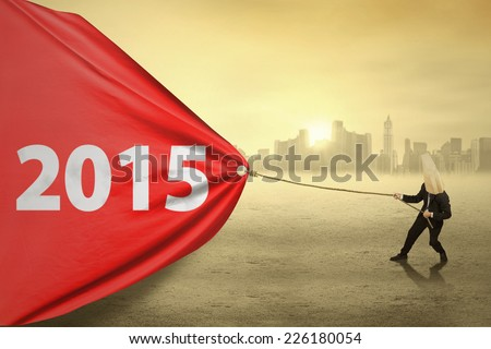 Anonymous person pulling number 2015 on a big banner in the morning - stock photo