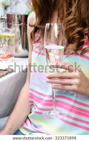 Anonymous redhead holding a champagne flute glass, celebrating a special occasion at a casual outdoor summer party