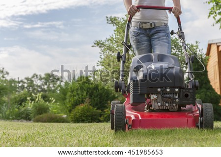 Anonymous woman mowing the lawn with a motorized lawnmower