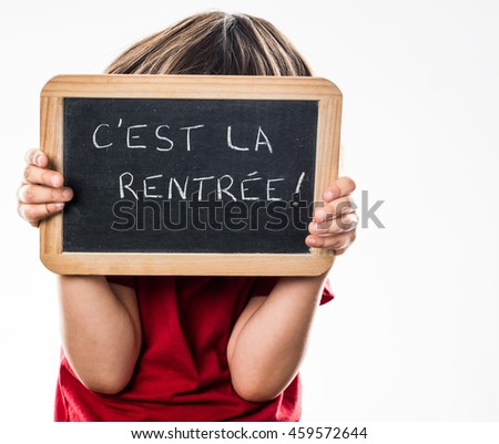 anonymous young child playing hide and seek behind a French writing slate, informing about a fun back to school, white background studio