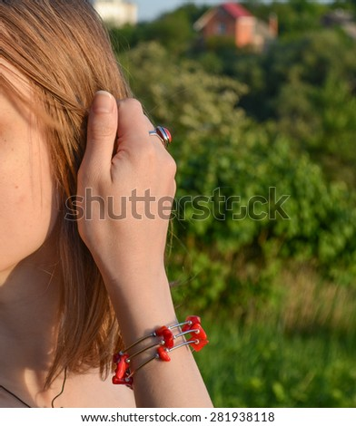 Anonymous young girl touching her hair with hand with coral ring and bracelet, outdoor summer background - stock photo