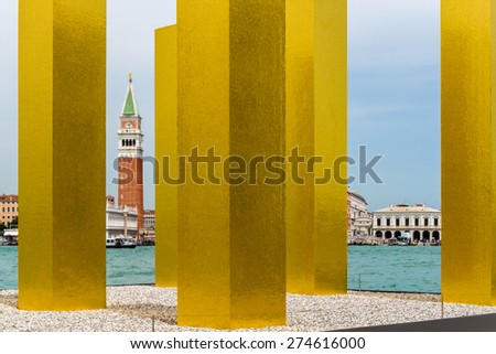 Another view to St. Mark's Square of Venice through recently erected, modern, golden-shimmering pillars representing modern arts. - stock photo