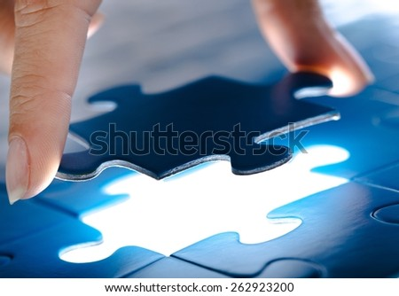 Answer. Missing jigsaw puzzle piece with light glow, business concept for completing the final puzzle piece  - stock photo