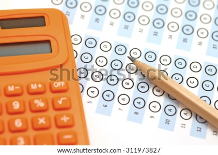 answer sheet test score with pencil and orange calculator