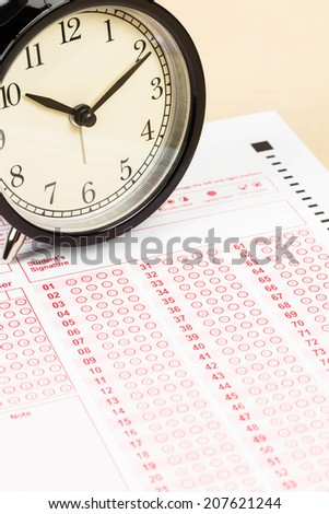 Answer sheet with alarm clock - stock photo