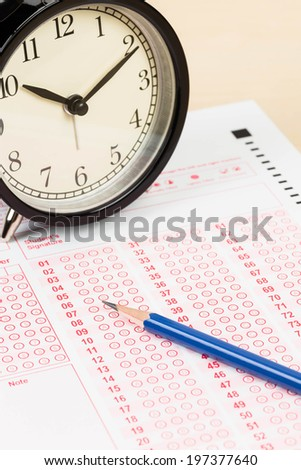 Answer sheet with pencil and alarm clock - stock photo