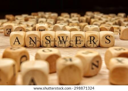 ANSWERS word written on wood block - stock photo