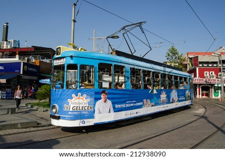 ANTALYA, TURKEY - AUGUST 18, 2014:  A tram traveling through the old town of Antalya with a poster for the city's mayor Menderes T�¼rel on the side.  - stock photo