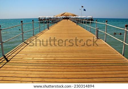 ANTALYA, TURKEY - AUGUST 13, 2008: Perspective view of wooden pier and deck on summer resort beach, Mediterranean sea, Antalya, Turkey. - stock photo