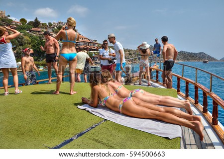 Antalya, Turkey - 28 august, 2014: Tourists on board leisure boat trip, passengers get tanned and photographed.
