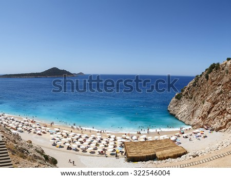 ANTALYA, TURKEY - JULY 19, 2015 : Top view of famous canyon junction beach of Antalya, Kaputas Beach with its turquoise water color, people swimming and sunbathing on bright blue sky background. - stock photo