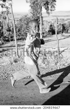 ANTANANARIVO, MADAGASCAR - JULY 3, 2011: Unidentified Madagascar boy runs happily smiling in the street. Children in Madagascar suffer of poverty due to slow development of the country