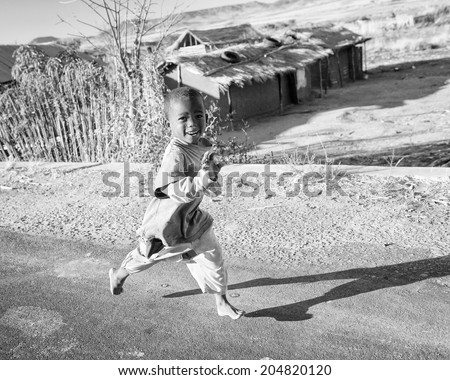 ANTANANARIVO, MADAGASCAR - JULY 3, 2011: Unidentified Madagascar boy runs happily smiling in the street. Children in Madagascar suffer of poverty due to slow development of the country - stock photo