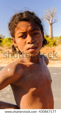 ANTANANARIVO, MADAGASCAR - JULY 3, 2011: Unidentified Madagascar boy runs near a road. People in Madagascar suffer of poverty due to slow development of the country