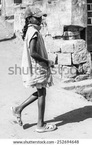 ANTANANARIVO, MADAGASCAR - JUNE 30, 2011: Unidentified Madagascar girl walks in the street. People in Madagascar suffer of poverty due to slow development of the country