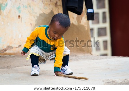 ANTANANARIVO, MADAGASCAR - JUNE 30, 2011: Unidentified Madagascar little boy plays with a stick. People in Madagascar suffer of poverty due to the slow development of the country