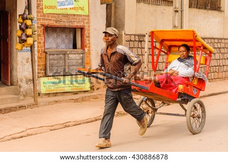ANTANANARIVO, MADAGASCAR - JUNE 30, 2011: Unidentified Madagascar man carries a carriage. People in Madagascar suffer of poverty due to the slow development of the country - stock photo