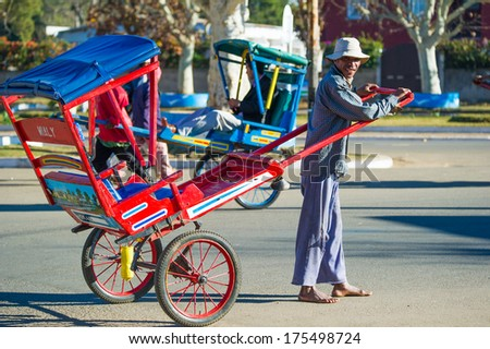 ANTANANARIVO, MADAGASCAR - JUNE 29, 2011: Unidentified Madagascar man carries a red carriage. People in Madagascar suffer of poverty due to the slow development of the country - stock photo
