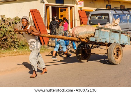 ANTANANARIVO, MADAGASCAR - JUNE 29, 2011: Unidentified Madagascar man carries  a transporting carriage with bags. People in Madagascar suffer of poverty due to the slow development of the country - stock photo
