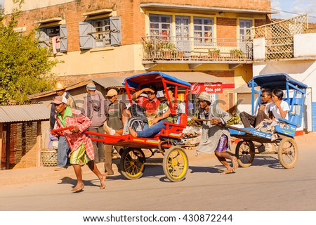 ANTANANARIVO, MADAGASCAR - JUNE 29, 2011: Unidentified Madagascar man carries  a transporting carriage. People in Madagascar suffer of poverty due to the slow development of the country - stock photo