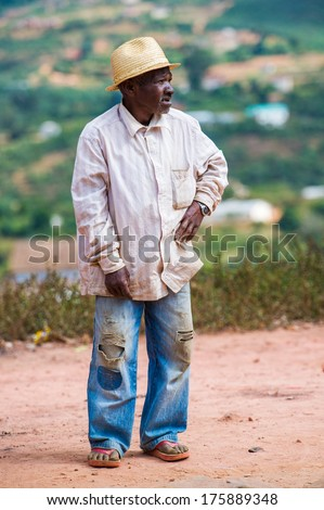 ANTANANARIVO, MADAGASCAR - JUNE 30, 2011: Unidentified Madagascar man in hat and white shirt stays and smiles. People in Madagascar suffer of poverty due to the slow development of the country - stock photo