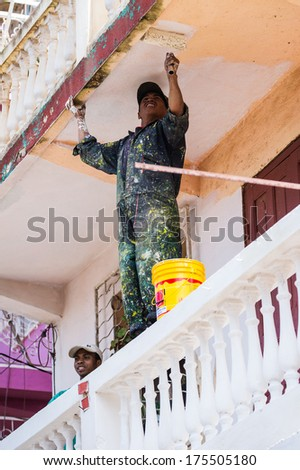 ANTANANARIVO, MADAGASCAR - JUNE 30, 2011: Unidentified Madagascar man paints the wall with white paint. People in Madagascar suffer of poverty due to the slow development of the country - stock photo