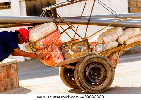 ANTANANARIVO, MADAGASCAR - JUNE 27, 2011: Unidentified Madagascar man pushes a carriage construction. People in Madagascar suffer of poverty due to the slow development of the country - stock photo