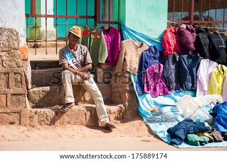 ANTANANARIVO, MADAGASCAR - JUNE 30, 2011: Unidentified Madagascar man sell clothes at the market and smiles. People in Madagascar suffer of poverty due to slow development of the country - stock photo