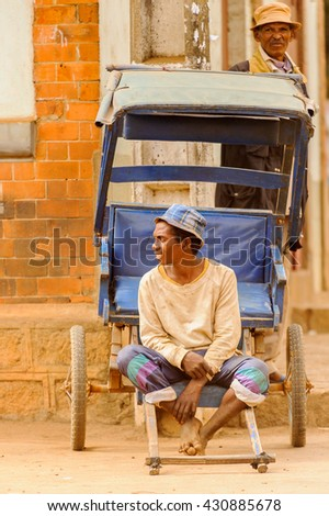 ANTANANARIVO, MADAGASCAR - JUNE 29, 2011: Unidentified Madagascar man sits on a tranport carrige. People in Madagascar suffer of poverty due to the slow development of the country - stock photo