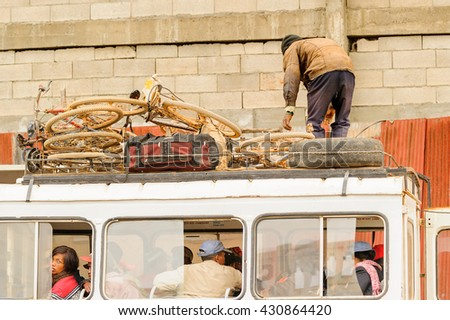 ANTANANARIVO, MADAGASCAR - JUNE 28, 2011: Unidentified Madagascar man transports bikes on a bus top. People in Madagascar suffer of poverty due to the slow development of the country - stock photo