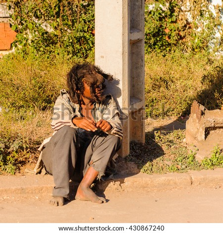 ANTANANARIVO, MADAGASCAR - JUNE 29, 2011: Unidentified Madagascar man with funny hair sits near the road. People in Madagascar suffer of poverty due to the slow development of the country - stock photo