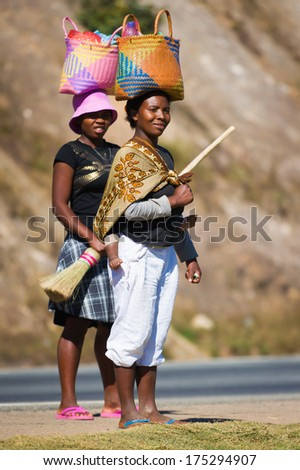 ANTANANARIVO, MADAGASCAR - JUNE 27, 2011: Unidentified Madagascar women walk and carry bags on their heads. People in Madagascar suffer of poverty due to the slow development of the country