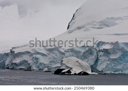 Antarctic coast with huge snow mountains and crevices