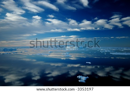 Antarctic iceberg  and cloud landscape reflecting in totally calm waters near Ross Island. Picture was taken during a 3-month research expedition to the formerly inaccessible Larsen area. - stock photo