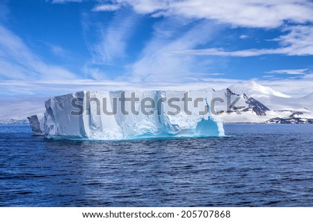 Antarctic iceberg floating in the ocean with beautiful background.