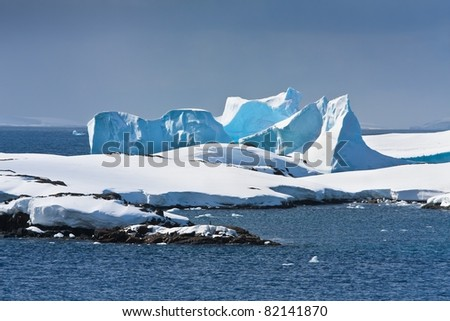 Antarctic iceberg in the snow. Beautiful winter background. - stock photo