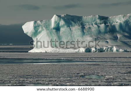Antarctic iceberg with adelie penguins - stock photo