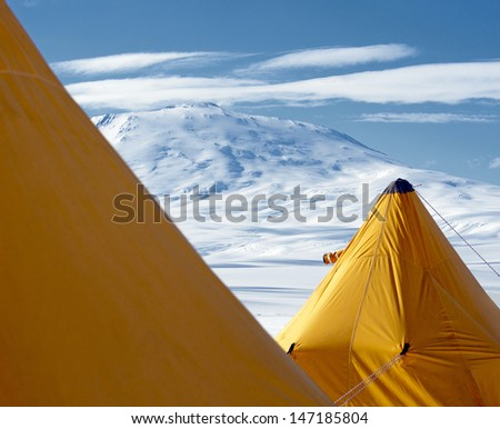 Antarctic landscape with yellow tents in the foreground