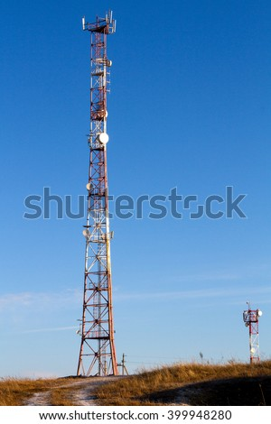 Antenna mast isolated on blue sky background. Telecommunication tower on a hill - stock photo