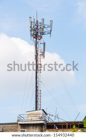 Antenna repeater installed on building rooftop on blue sky - stock photo