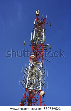 Antenna tower with various telecommunications equipment on it.