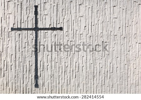 Anthracite cross made of metal on a white wall with very coarse texture  - stock photo