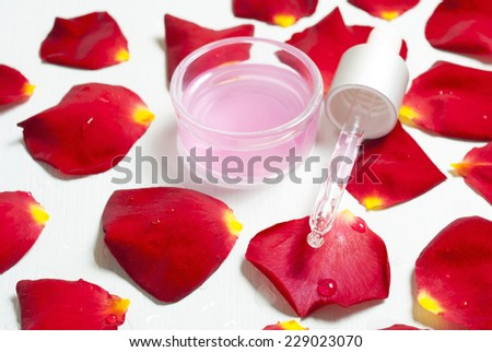 anti aging elixir with a pipette and red rose petals on white wooden