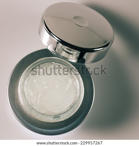 Anti-aging serum in opened glass jar.