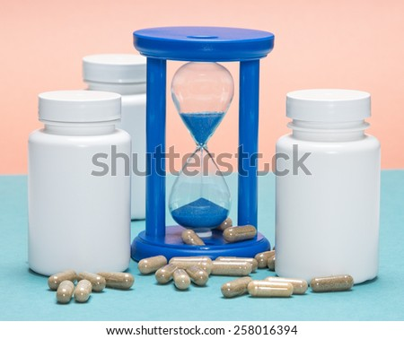 Anti-aging supplements concept: scattered capsules with white plastic jars and hourglass - stock photo
