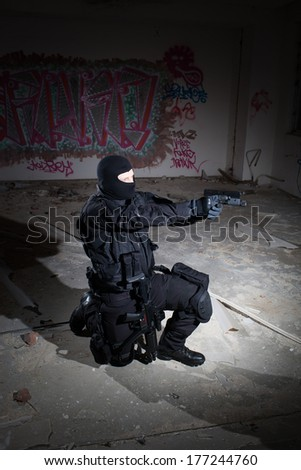 Anti terrorist unit policeman/soldier during the night operation/mission in criminal's house aiming at target (very harsh lighting is used on this shot to underline the atmosphere of night mission) - stock photo