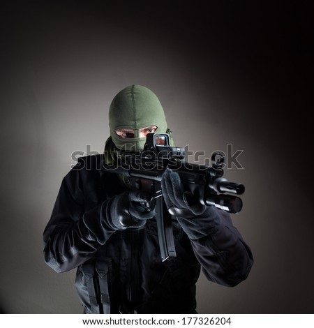 Anti terrorist unit policeman/soldier during the night strike/operation in criminal's house aiming at the target (very harsh lighting is used on this shot to underline the atmosphere of night mission) - stock photo